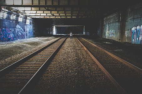 man, standing, middle, underground, train, rails, graffiti