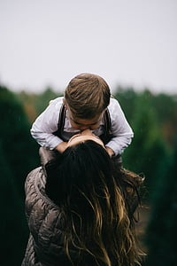 woman, black, bubble, jacket, carrying, boy, kissing
