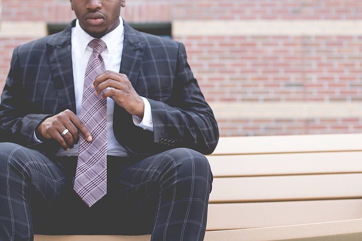 man, black, grey, checked, suit, sitting, holding