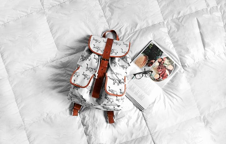 backpack, bed, book, eyeglasses, white