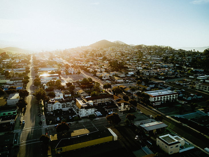city, buildings, roads, mountains, sun, community, cityscape