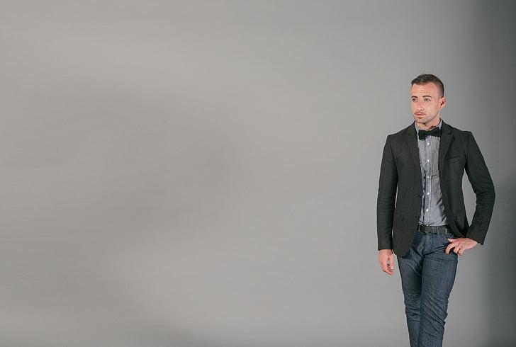 man, black, blazer, jeans, standing, gray, background