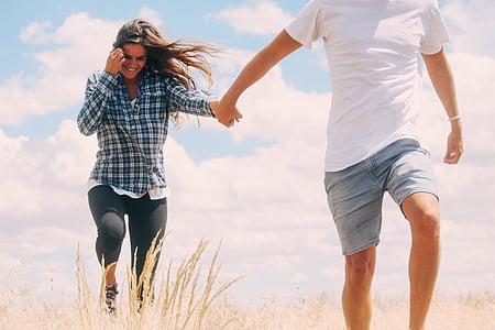 man, woman, walking, filed, sky, clouds, grass