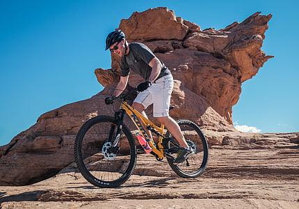 man, black, shirt, riding, bicycle, near, rock