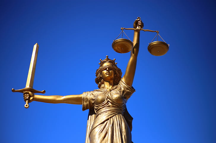 Golden statue of Lady Justice blindfolded with her scales and sword