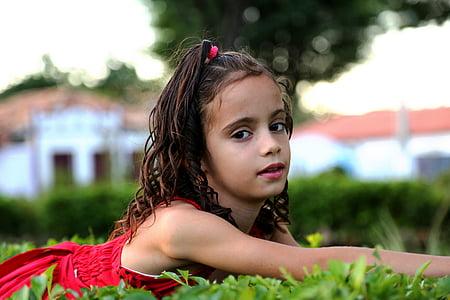 nena mirant de perfil, noia al jardí, model de, nen, família, herba verda, vestit vermell