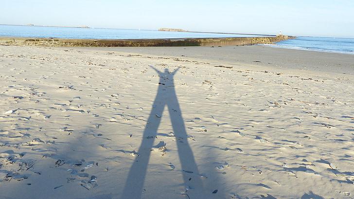 Shadow mannen, människans skugga i sand, skuggspel, havet, stranden, naturen, kusten